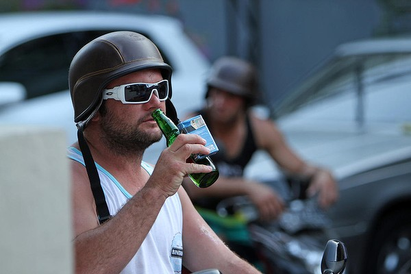 Tourist on bike with helmet, beer and cigarettes in right hand