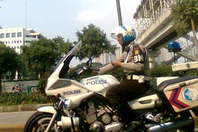 Indonesian policemen using mobile while driving